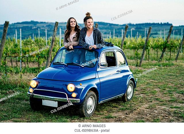Tourists standing through car sunroof, vineyard, Tuscany, Italy