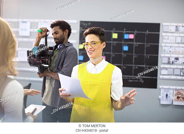 Female vlogger and cameraman preparing in office