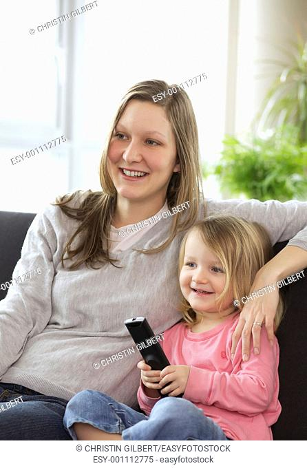 Young mother and daughter watching TV together in the living room