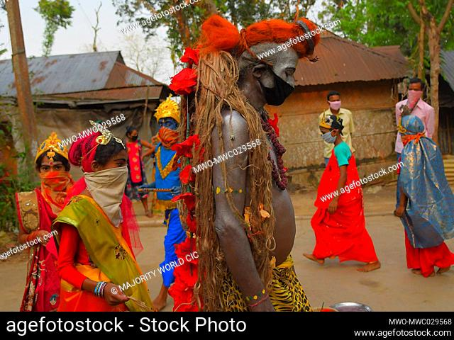 AGARTALA, TRIPURA, INDIA, 12-04-2020 : Folk artists are performing the rituals of Shiber Gajan with covering the face with cloth and mask