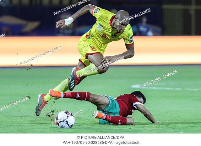 05 July 2019, Egypt, Cairo: Morocco's Mbark Boussoufa and Benin's Jordan Adeoti (Up) battle for the ball during the 2019 Africa Cup of Nations round of 16...
