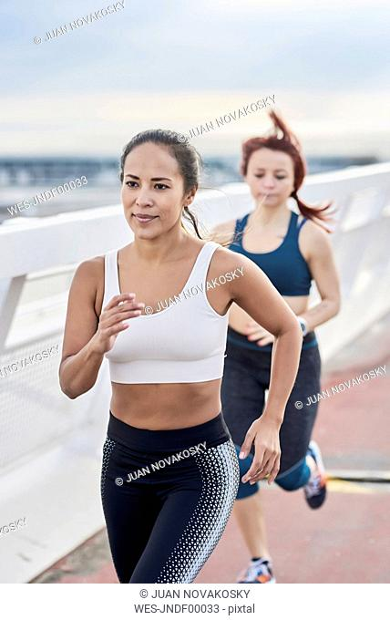 Female athletes running on a bridge
