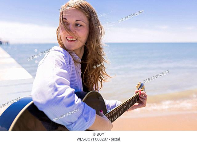 Smiling young woman with guitar at seaside
