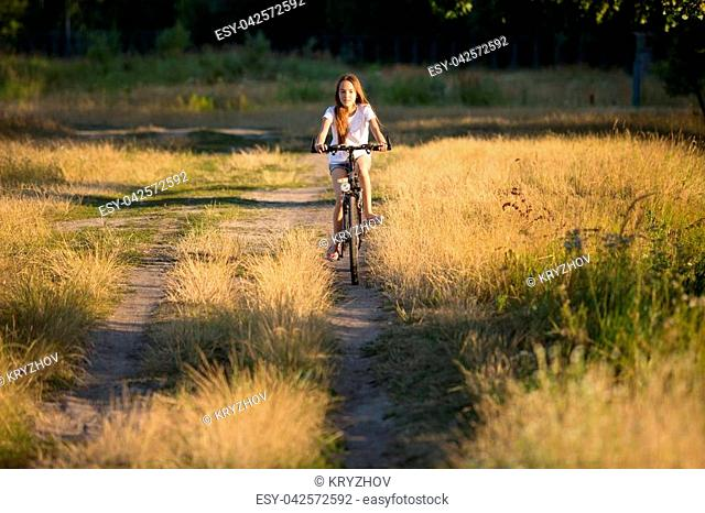 Young girl riding bicycle in field at sunset