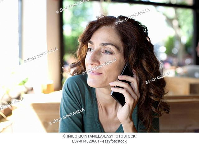 portrait of woman with green shirt curly brunette hair with listen to mobile phone in ear sitting inside light brown wooden cafe