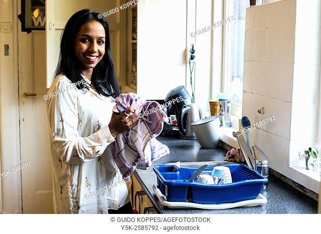 Tilburg, Netherlands. Young, dark skinned woman doing the dishes after lunch, inside her kitchen at home