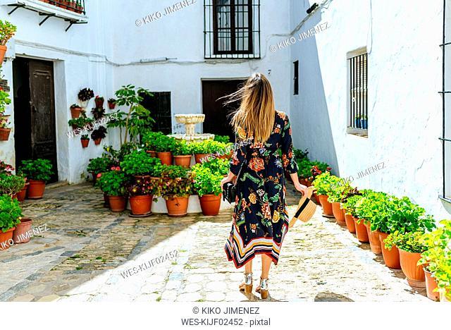 Spain, Cadiz, Vejer de la Frontera, back view of fashionable woman standing at patio