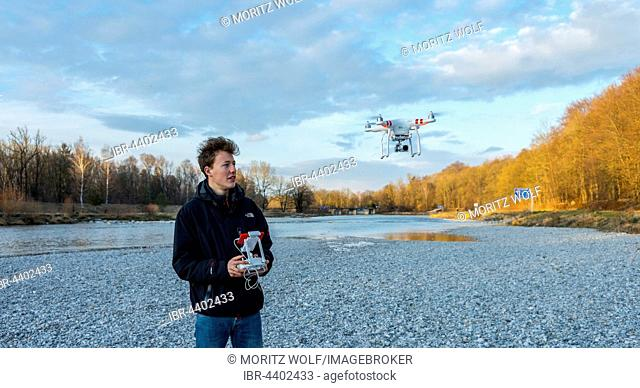Young man controlling quadcopter, drone with camera flying, DJI Phantom 3, Munich, Upper Bavaria, Bavaria, Germany