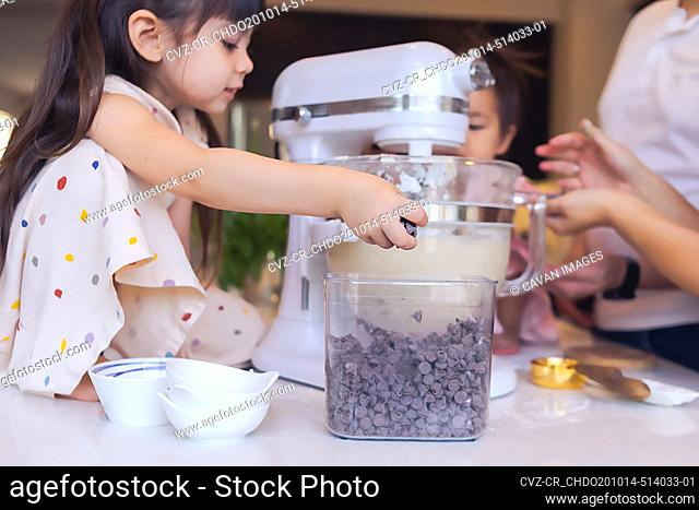 Preschooler baking with her family, adding chocolate chips to mixer