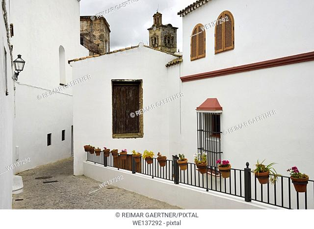 Maldonado street to church of Saint Peter with whitewashed houses and flowers in clay pots Arcos de la Frontera Spain