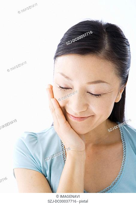 A woman touching her cheek