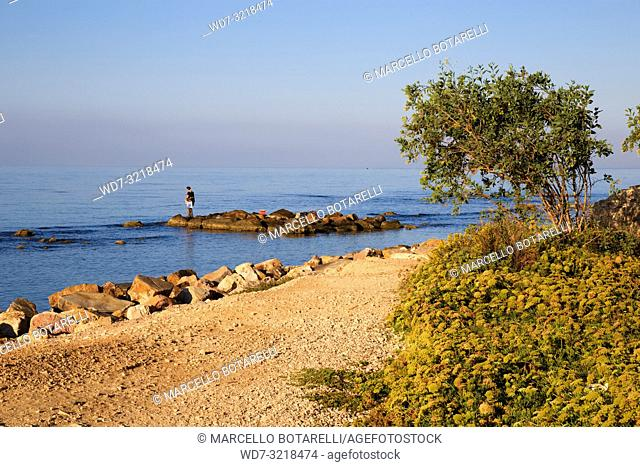 rocks by the sea of Santa Severa, fisherman on the rocks, near Rome, Italy