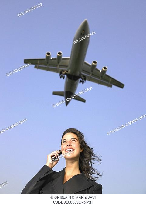 Woman on cellular phone smiling with plane flying overhead