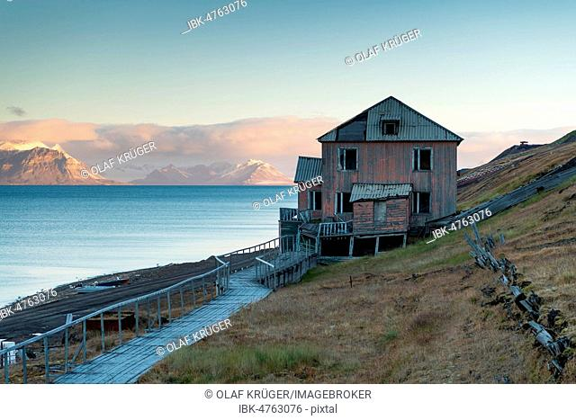 Vacant, dilapidated residential building at dawn, Russian miners' settlement Barentsburg, Isfjorden, Spitsbergen, Svalbard, Norway
