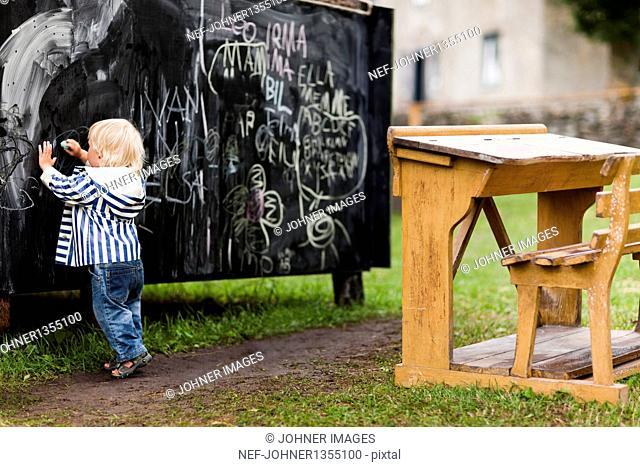 Baby boy writing on blackboard in backyard