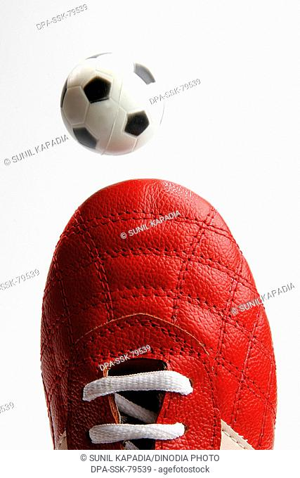 Red shoe and small white and black rubber ball of soccer or football sport