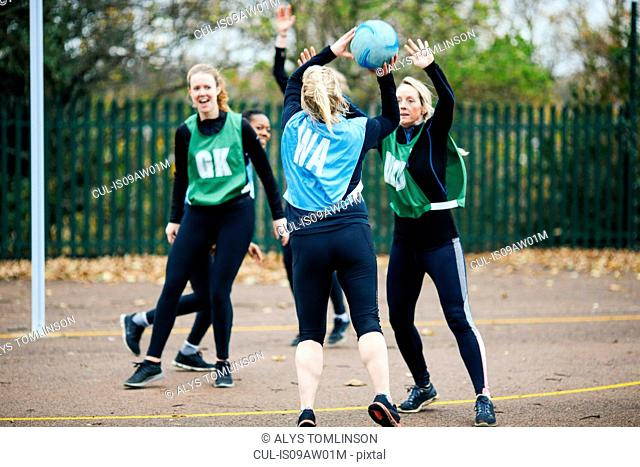 Female netball teams playing match on netball court