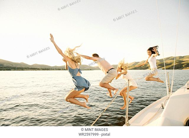 Four people jumping off the side of a sail boat into a lake