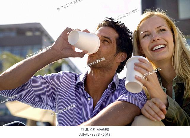 Couple drinking take out coffee outdoors