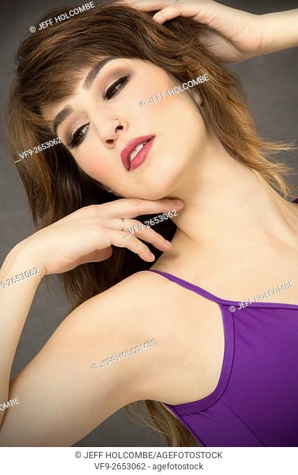 Portrait of attractive young woman in purple leotard, looking down with head tilted and hand in hair