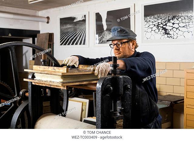 Germany, Bavaria, Mature man working on copperplate printing machine at print shop
