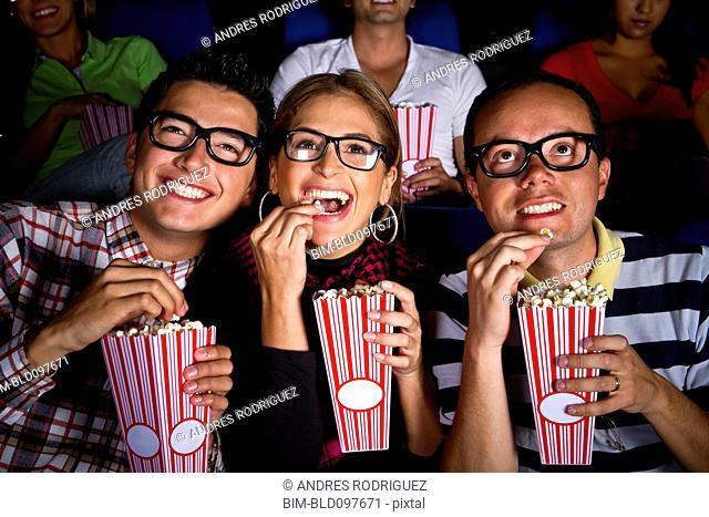 Hispanic friends enjoying popcorn at movie theater