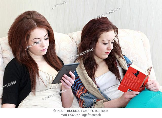 UK Great Britain Europe Two teenage twin girls aged 15 years one reading a Kindle and the other reading a paperback book whilst sitting on a sofa together