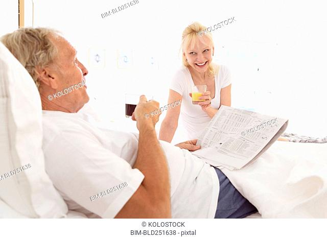 Caucasian couple drinking coffee and juice in bed