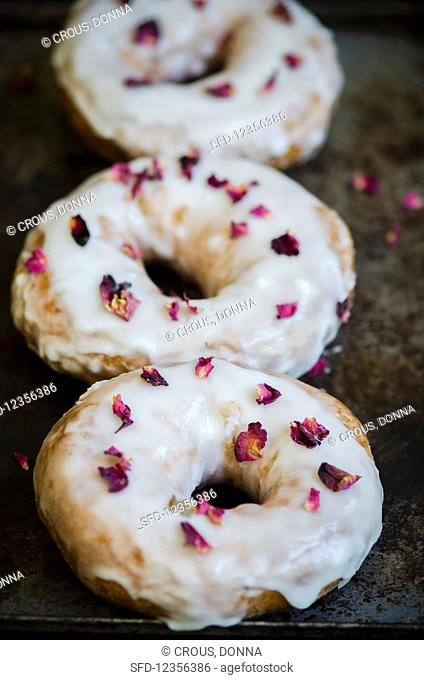 Three doughnuts sprinkled with dried rose petals