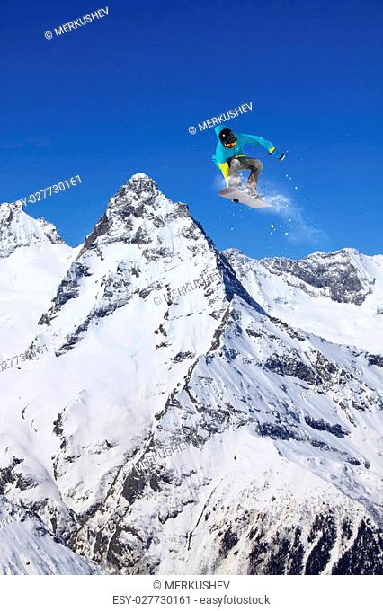 Snowboard rider jumping on winter mountains. Extreme snowboard freeride sport