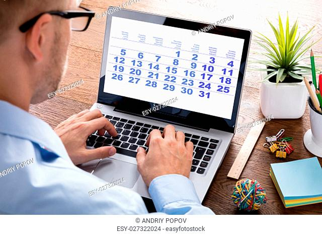 Close-up Of A Business Person Looking At Calendar With Daily Agenda On Laptop Computer