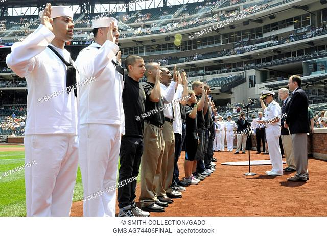Several service members and Delayed Entry Program members recite the Oath of Enlistment with Rear Admiral Herman A Shelanski