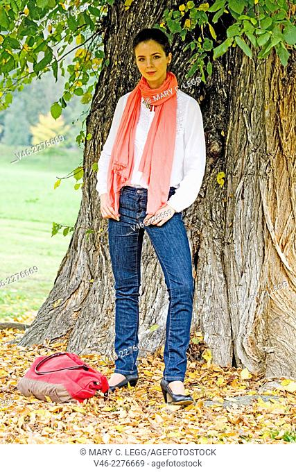 Woman with red bag under large tree. Woman in white blouse and dark blue jeans with coral scarf stands under a large tree