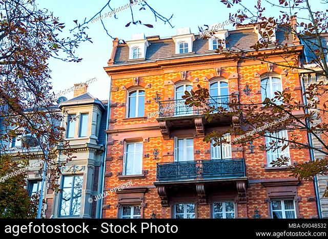 Historic red brick townhouse in Strasbourg, Alsace, France in the evening light framed between the branches of two trees