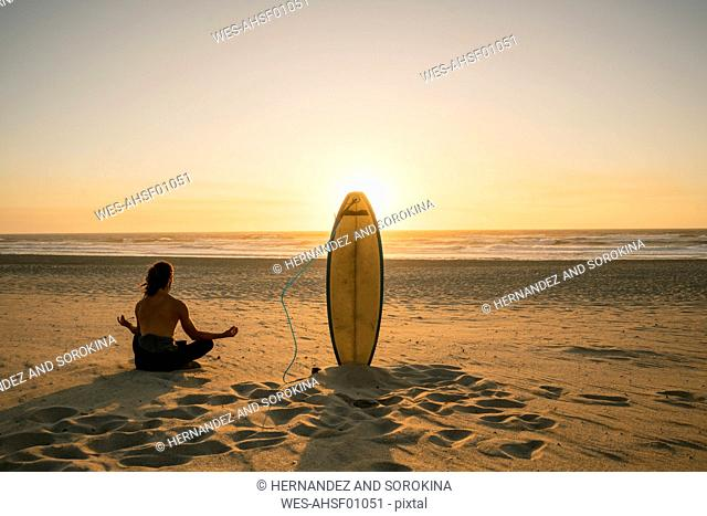 Rear view of a surfer doing meditation during the sunset at the beach