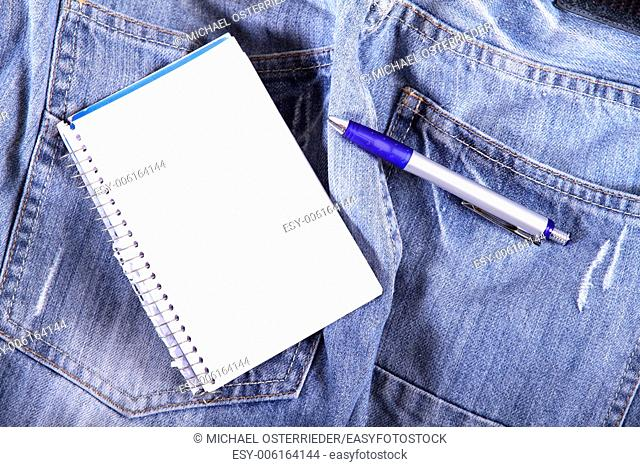 A notebook on some jeans trousers