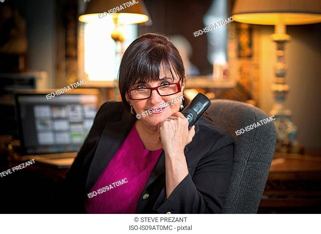 Portrait of senior woman in office, using telephone