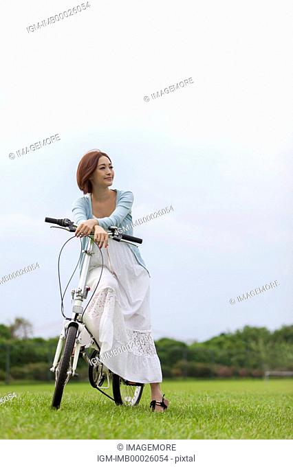 Young woman sitting on the bicycle and looking away with smile