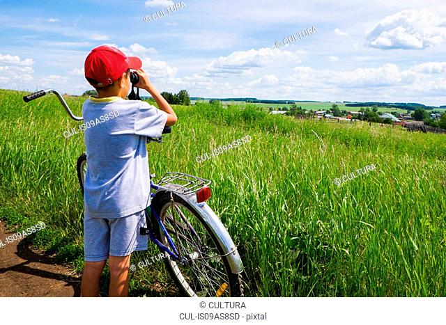 Young boy standing with bicycle beside field, looking at landscape through binoculars, rear view