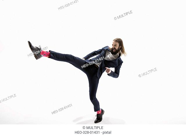 Aggressive businessman with beard kicking in fighting stance against white background