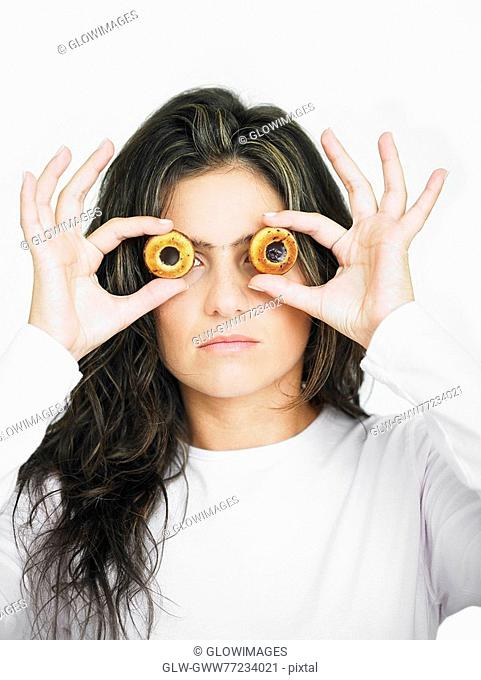 Young woman looking through the center of two cookies
