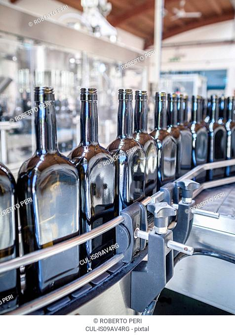 Rows of bottles on production line in factory
