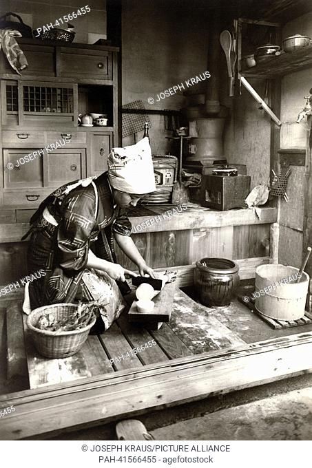 A woman cuts a radish - Daigon - in her kitchen. Pictured in the early 1920th. - /Japan