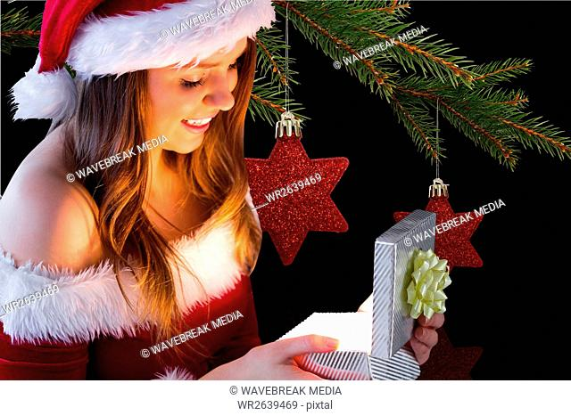 Woman in santa costume looking at christmas gift