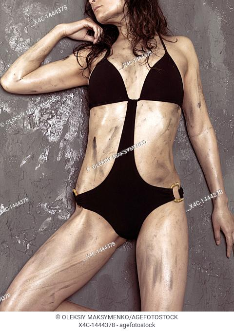 Beautiful young woman with shiny soiled body wearing a trendy swimsuit