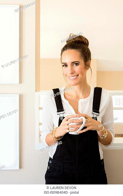Portrait of beautiful female fashion and lifestyle blogger holding coffee cup