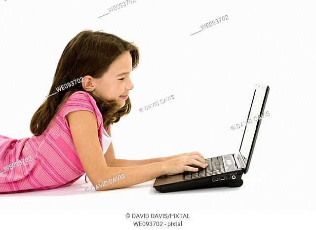 Child laying on a white background working on laptop computer