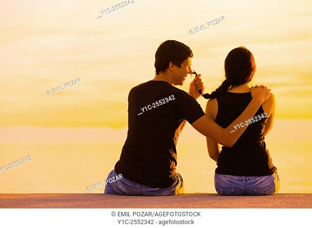 Happy teen couple in sunset he teases her