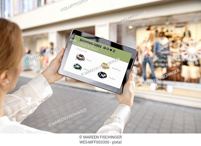 Woman holding a digital tablet with with online shopping app