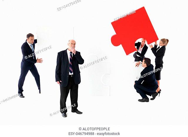 Business team assembling big puzzle